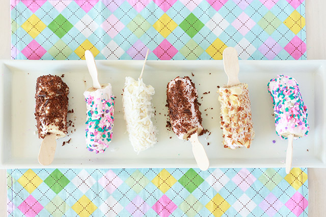 frozen banana pops on a white tray with different toppings: sprinkles, coconut, chocolate pieces, nuts